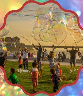 dzieci bawiące się na trawniku wśród wielkich baniek mydlanych, w tle rzeka, kolorowa ramka wokół